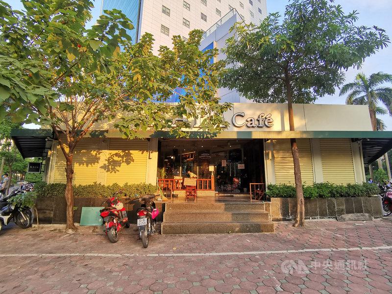 越南首都河內市連續多天出現COVID-19本土病例,13日再增8人染疫,全市再度暫停餐飲內用、理髮服務。圖為河內市一家咖啡廳拉下鐵門,只留下外送咖啡的出入口。中央社記者陳家倫河內攝 110年7月13日