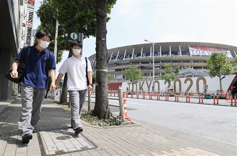 日本東京都14日新增1149例確診病例,繼5月8日以來再度出現單日新增逾千例。圖為7月12日民眾行經奧運主場館週邊。(共同社)