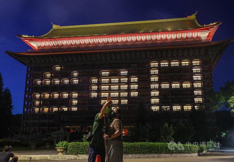日本3度捐贈AZ疫苗給台灣,台北圓山大飯店15日晚間在外牆點亮「台愛日」表達對日方的感謝,有民眾戴著口罩在飯店外開心自拍。中央社記者鄭清元攝 110年7月15日