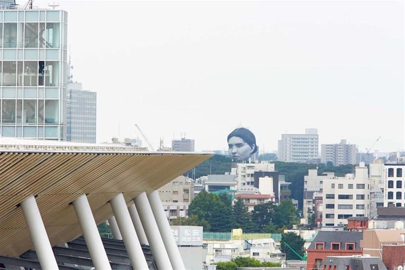 日本東京都上空16日出現一個巨大人頭熱氣球,引起民眾圍觀,形容宛如恐怖漫畫大師伊藤潤二的作品「人頭氣球」;其實這是東京奧運的現代藝術活動。(圖取自twitter.com/TTF_official_PR)