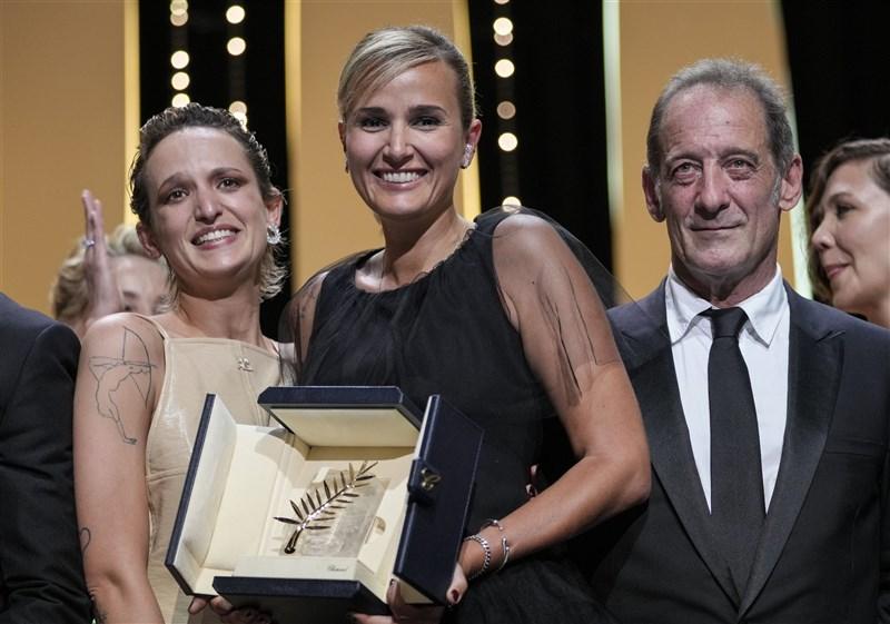 法國女導演茱莉亞迪古何諾(中)執導的電影「鈦」17日在第74屆坎城影展奪得最佳影片金棕櫚獎,她獲獎後與「鈦」主角阿加特羅素(前左)、文森林敦(前右)合影。(美聯社)