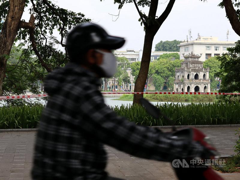 越南首都河內市19日新增44例COVID-19本土病例,知名景點還劍湖四周全拉起封鎖線,不讓民眾散步聚集。圖為一名機車騎士經過被封鎖線圍住的還劍湖。中央社記者陳家倫河內攝 110年7月19日