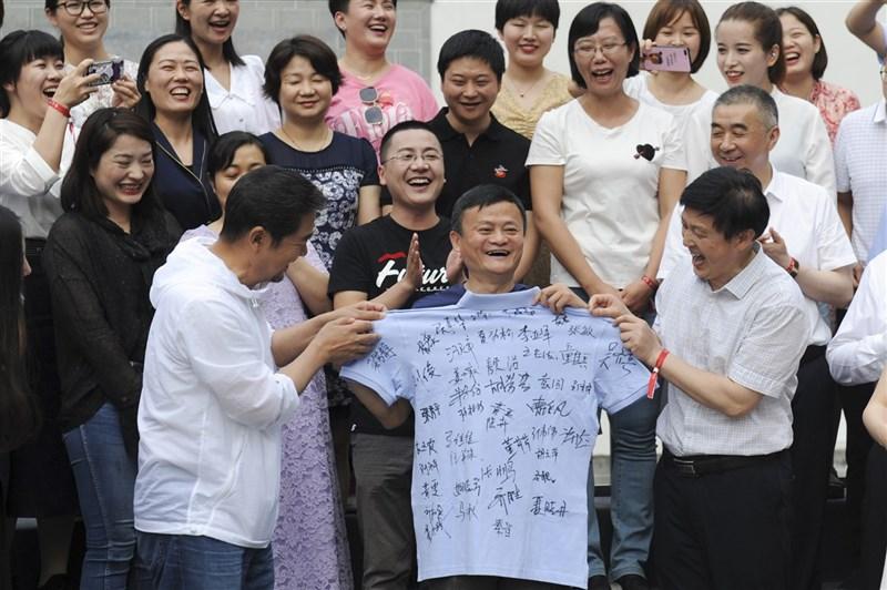 富比世(Forbes)中國20日發布「2021中國慈善榜」,阿里巴巴集團創辦人馬雲去年捐款位列榜首。圖為2020 年6月6日,馬雲(前中)請安徽援鄂醫療隊吃火鍋,醫療隊為馬雲送上簽名隊服。(中新社)
