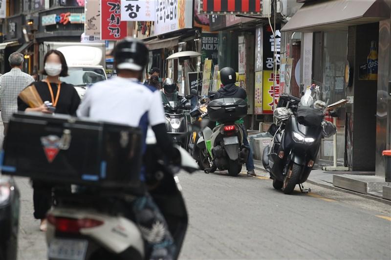 據韓國防疫當局統計,20日凌晨零時至下午6時間COVID-19確診案例累計1442例,逼近13日1615例的最高紀錄。圖為19日首爾街頭繁忙的外送員。(韓聯社)