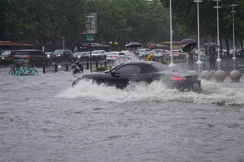 中國河南省近日遭遇極端暴雨,多地降雨量打破歷史紀錄,省會鄭州市已陷入一片汪洋,災情慘重。圖為20日鄭州市車輛行經淹水處。(中新社)