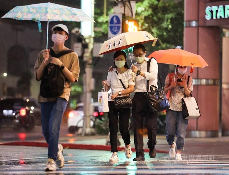 颱風烟花逼近,中央氣象局21日晚間9時20分針對北北基等6縣市發出大雨特報。台北市區入夜後風雨變得明顯,街頭有民眾在雨中共撐一把傘。中央社記者鄭清元攝 110年7月21日