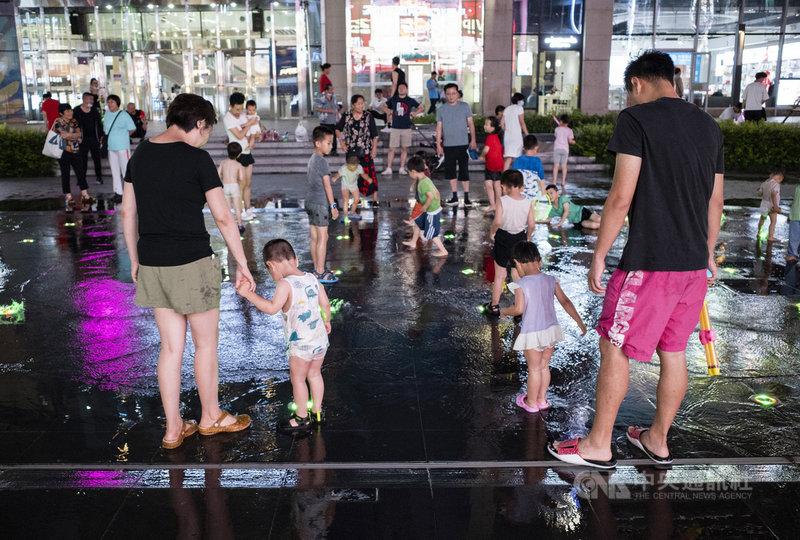 中國5月底開放生育三孩後,中國國家衛健委官員21日指出,今年的出生人口和生育水平仍然呈現走低的趨勢。圖為20日晚間,市民帶著孩子在北京朝陽區望京小街的噴泉玩耍。(中新社提供)中央社 110年7月21日