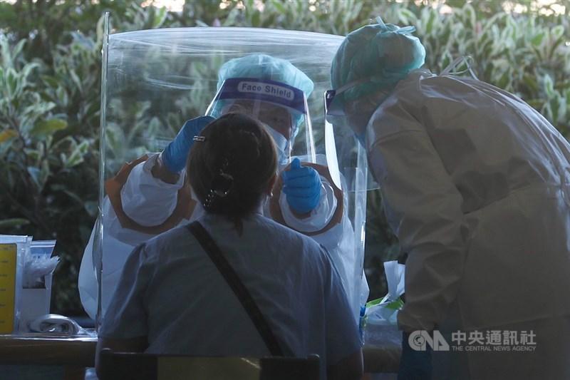 台北市東湖市場一名豬肉攤販20日確診,副市長黃珊珊說,這名個案的CT值為36,匡列21名接觸者中9人PCR為陰性,另外12人則尚未出爐。圖為醫護人員替民眾採檢。(中央社檔案照片)