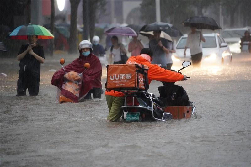 中國河南省近日降下暴雨,鄭州市城區20日嚴重淹水。圖為鄭州市民20日傍晚在暴雨中涉水前進。(中新社)