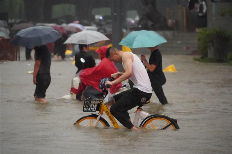 中國河南省近日遭遇大暴雨,各項災情持續傳出。圖為鄭州市民眾20日冒著道路淹水上路。(中新社)
