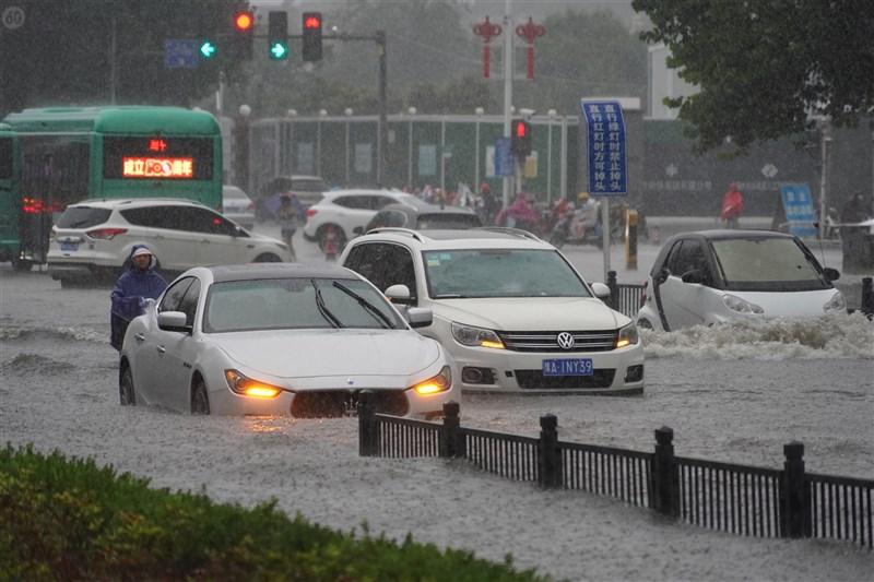 中國河南省20日遭逢大暴雨,致使當地交通中斷受阻。鄭州機場21日中午12時前不接受進港航班。圖為鄭州民眾駕車行駛在積水路面。(中新社)