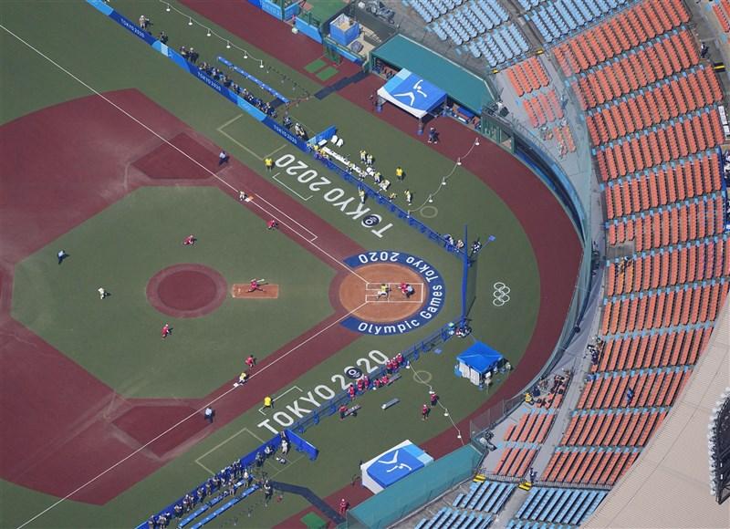 日本東京奧運首場比賽的壘球賽事,21日在福島縣營吾妻球場舉行,受疫情影響採閉門舉行,觀眾席上空無一人。(共同社)