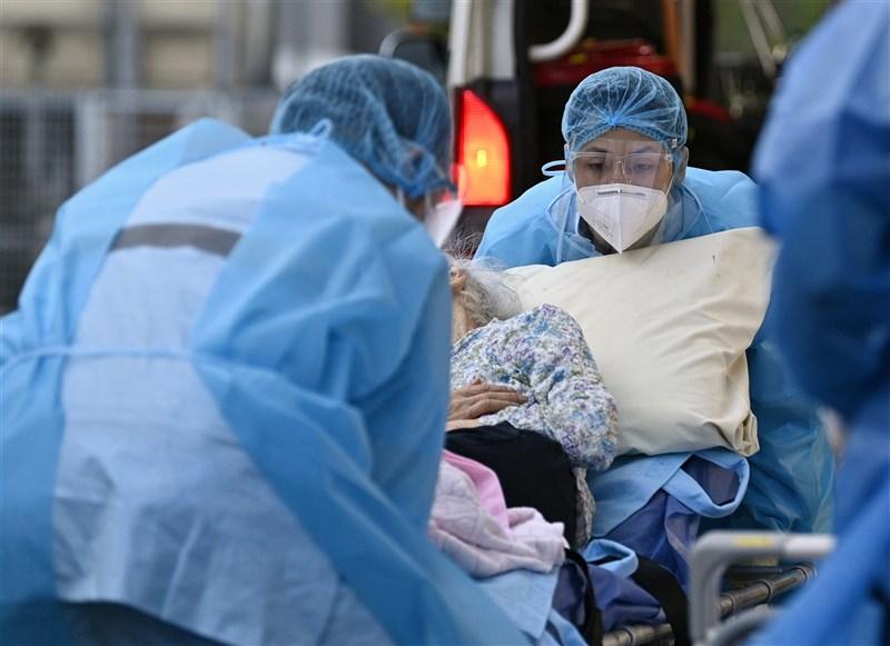 瑞士製藥巨擘羅氏藥廠20日表示,日本全面核准羅氏的抗體療法Ronapreve,治療感染COVID-19輕中症病患。圖為日本染疫患者搭乘救護車就醫。(共同社)