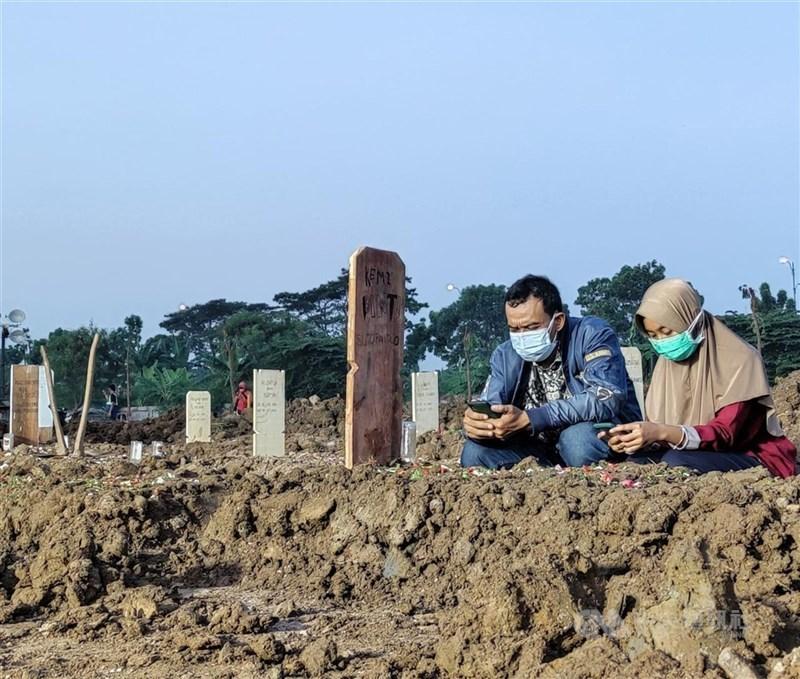 印尼疫情嚴峻,一個月新增100萬例確診感染COVID-19,累計已300萬人確診。單日死亡人數22日再創新高,近9日已超過萬人不治。圖為9日印尼民眾在墓園追思親人。中央社記者石秀娟雅加達攝 110年7月22日