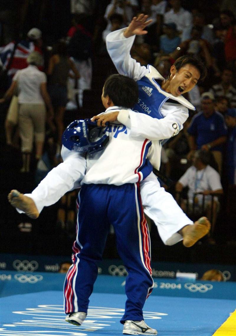 「台灣戰神」朱木炎2004年在雅典奧運摘下男子跆拳道第一量級(58公斤以下)金牌,開心地與教練在台上相擁。(中央社檔案照片)