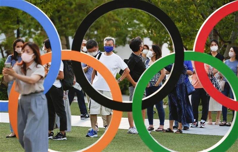 東京奧運開幕倒數,日本進入第5波疫情,各國代表團選手相繼確診。圖為21日民眾在東奧主場館國立競技場附近的奧運標誌合影。(共同社)