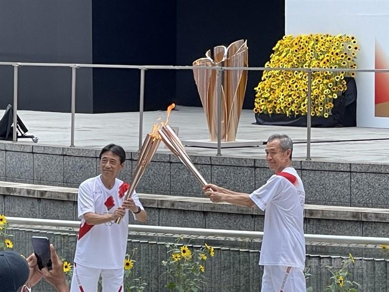 東京奧運聖火23日抵達最後一站都廳前,跑者以「火炬接吻」形式傳遞。中央社記者楊明珠東京攝 110年7月23日
