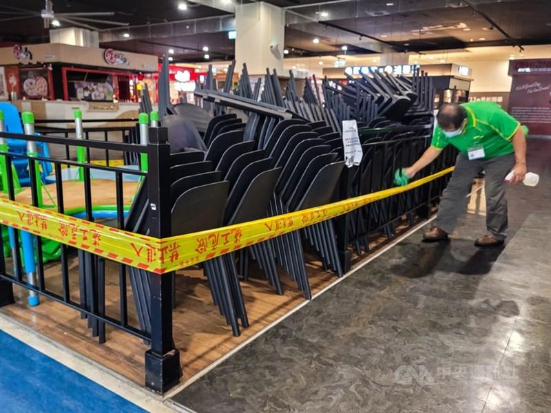 台灣自27日起調降為二級警戒,政院官員表示,集會活動人數上限將放寬至室內50人、室外100人,餐飲業若有適當防疫措施,也可開放內用,且經溝通,地方對此通案原則並無意見。圖為新北市一家大賣場美食街,工作人員清潔、消毒收起的餐桌椅。中央社記者鄭清元攝 110年7月23日