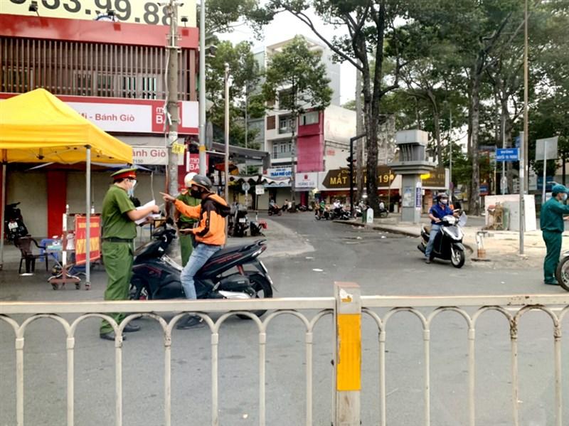 越南22日通報新增6164例COVID-19本土病例,創下紀錄新高,其中胡志明市有4000多人染疫。圖為胡志明市警方12日在路上攔查民眾、檢查外出文件。(讀者提供)