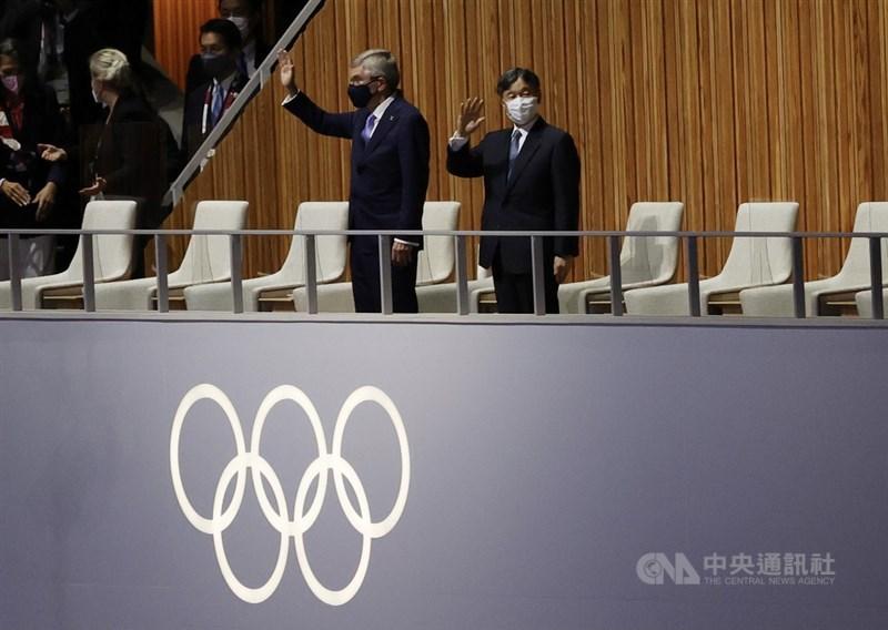 因疫情延後1年舉行的東京奧運,23日晚間在日本新宿國立競技場舉行開幕式,日本天皇德仁(右)及國際奧會(IOC)主席巴赫(Thomas Bach)(右2)出席,揮手致意。中央社記者吳家昇攝 110年7月23日