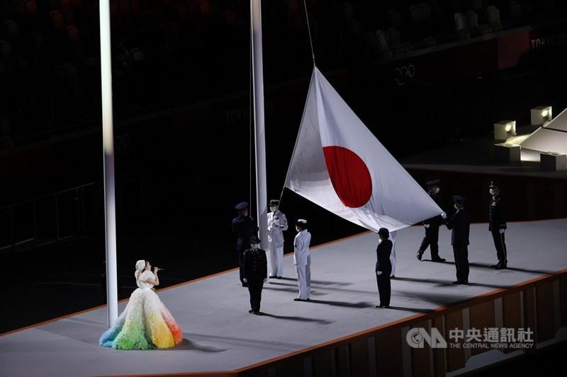 因疫情延後一年舉行的東京奧運,23日晚間在日本新宿國立競技場舉行開幕式,主辦國日本的國旗也在場內緩緩升起。歌手米希亞(左1)演唱日本國歌。中央社記者吳家昇攝 110年7月23日