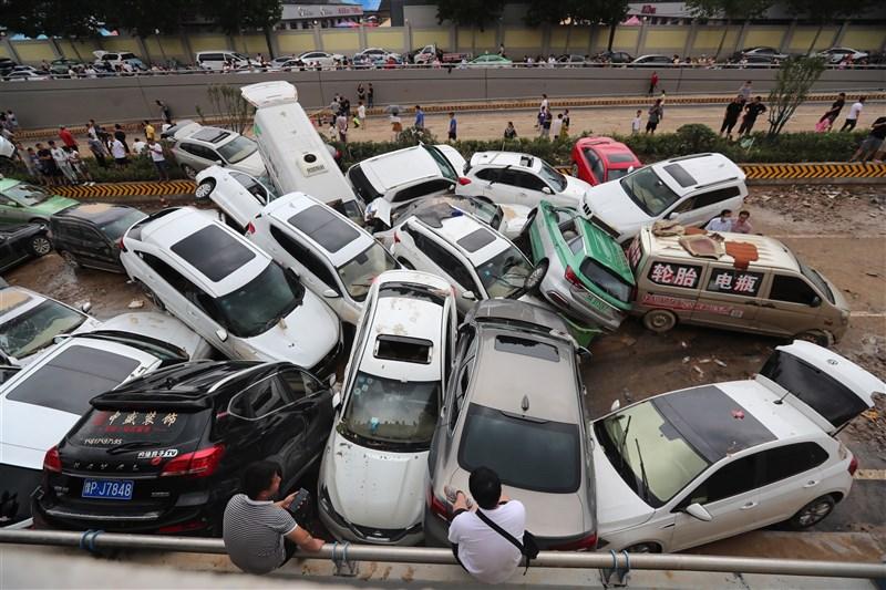 河南20日大暴雨,鄭州市京廣隧道幾乎被淹沒。圖為22日暴雨停止後,人們到隧道口處尋找自己的汽車。(中新社)
