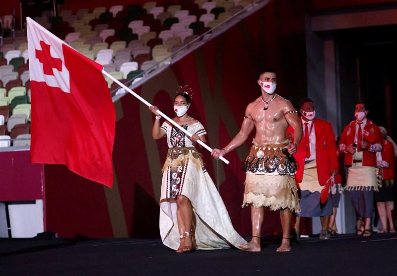 陶法托法(前右)在2016年里約奧運擔任東加王國掌旗官時,穿著東加王國傳統服飾,露出結實上半身進場,引發話題。陶法托法今年登場造型和當時一模一樣。(圖取自twitter.com/Tokyo2020)