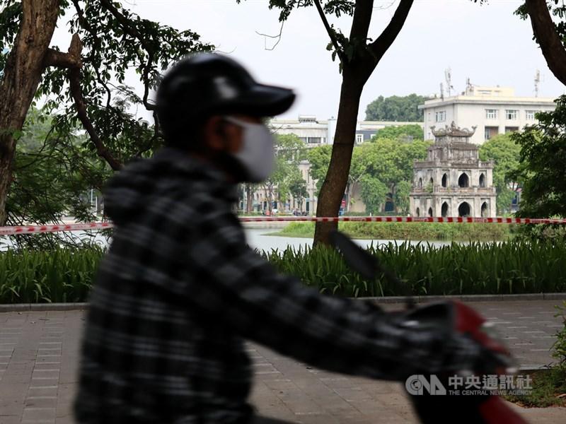 由於COVID-19疫情持續蔓延,越南24日宣布封鎖擁有800萬人口的首都河內。圖為19日一名機車騎士經過被封鎖線圍住的還劍湖。中央社記者陳家倫河內攝 110年7月19日