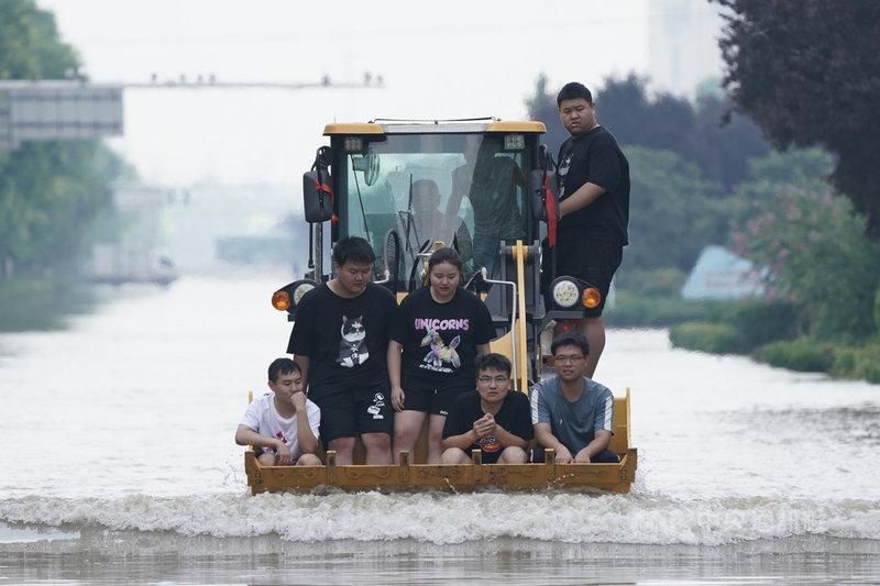 河南連日大暴雨。24日在河南新鄉市,民眾乘坐挖掘機通過新中大道一處涉水路段。(中新社提供)中央社  110年7月24日