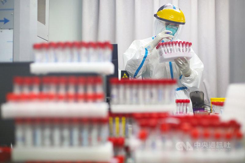 中國南京市20日爆發本土疫情後,迄今已蔓延5省。南京昨晚已完成全市第一輪普篩,圖為24日,南京市第一醫院工作人員在核酸檢測實驗室內對大量的核酸樣本展開檢測。(中新社提供)中央社 110年7月24日