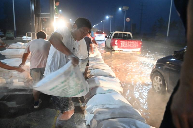 河南連日大暴雨,23日衛河河南新鄉段等部分河段出現險情。當日夜間,當地村民在G107國道新鄉段壘築堤壩抵禦洪水。(中新社提供)中央社 110年7月24日