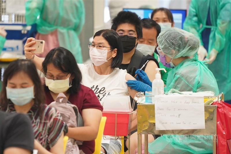 中央流行疫情指揮中心公布,23日接種逾25萬劑疫苗,疫苗人口涵蓋率達26%。圖為接種者拿起手機自拍留念。(中央社檔案照片)