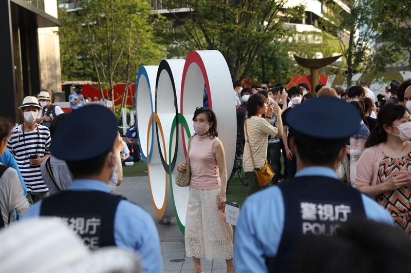 日本東京奧運24日再出傳有選手及警察感染COVID-19,東京都疫情仍未趨緩。圖為民眾跟奧運五環合影留念。(中央社檔案照片)