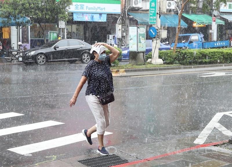 中央氣象局表示,受到西南風影響,中南部未來一週都要注意局部大雨。圖為未帶雨具民眾午後在大雨中快跑行進。中央社記者張新偉攝 110年7月23日