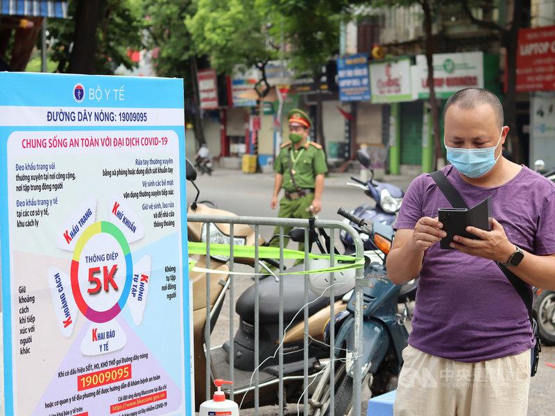 越南27日新增7911例COVID-19本土病例,連續5天單日新增確診數都超過7000人。圖為戴著口罩的越南民眾與防疫宣導招牌。中央社記者陳家倫河內攝 110年7月27日
