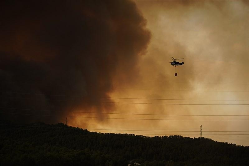 歐洲大陸今年夏天除飽受高溫、乾旱和暴雨所苦之外,還有野火肆虐。圖為25日西班牙東北部城鎮塔拉戈納附近遭野火肆虐。(美聯社)