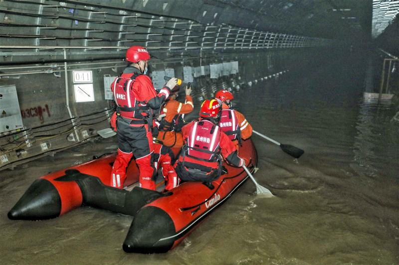 河南鄭州官方27日發布,20日晚發生的地鐵淹水事故共有14人遇難。圖為26日救援人員在鄭州地鐵5號線勘查積水情形。(中新社)