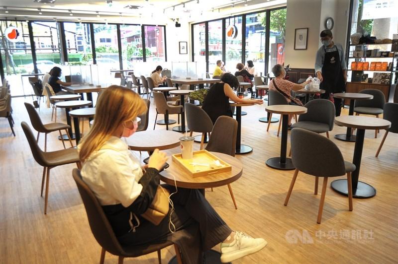 國內COVID-19疫情趨緩,疫情警戒27日起降為二級,桃園市一間連鎖咖啡店開放民眾入內消費,店裏排好梅花座,桌上也放置隔板,維持安全距離。中央社記者施宗暉攝 110年7月27日