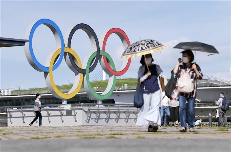日本中央政府擬30日將首都圈3縣(神奈川縣、埼玉縣、千葉縣)納入緊急事態宣言對象地區。圖為16日民眾行經神奈川縣橫濱市的奧運標誌旁。(共同社)