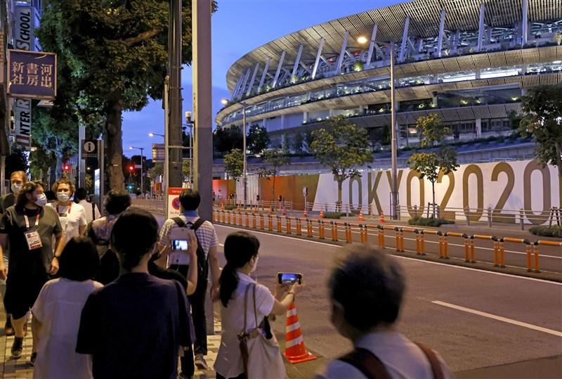 東京奧運選手村有8成以上運動員和教練接種疫苗,且大會嚴格限制移動,與場外逐漸鬆續防疫的民眾形成巨大對比。圖為27日晚間在東奧主場館國立競技場附近的人潮。(共同社)