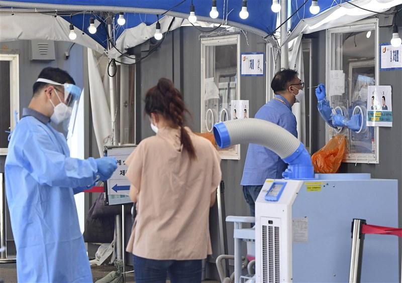 韓國疾病管理廳通報,韓國27日新增1896起COVID-19確診病例,創下單日最高紀錄。圖為26日首爾民眾在COVID-19檢測站接受採檢。(共同社)
