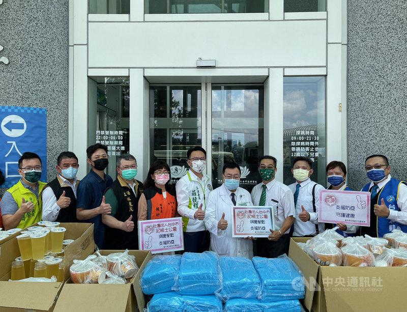民進黨籍立委莊競程(左6)等人媒合企業,捐贈200件防護衣、100份火鍋套餐、飲料等物資給台中慈濟醫院,為醫護人員加油。中央社記者趙麗妍攝  110年7月29日