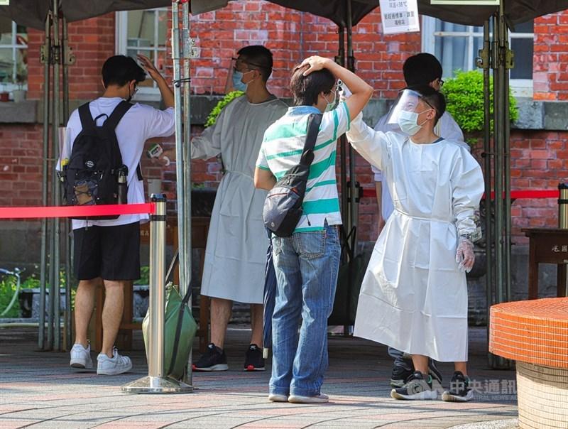 大學指考29日進行第2天考試,因應COVID-19疫情,工作人員穿防護衣、戴面罩,幫進入考場的學生量體溫。中央社記者謝佳璋攝 110年7月29日