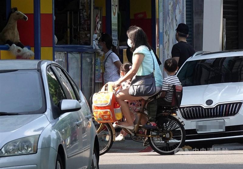 中央流行疫情指揮中心指揮官陳時中29日重申,COVID-19疫情控制不以零確診為目標,不會有潛藏案例未報出來。圖為29日家長騎腳踏車帶著小孩前往學校。中央社記者鄭傑文攝 110年7月29日