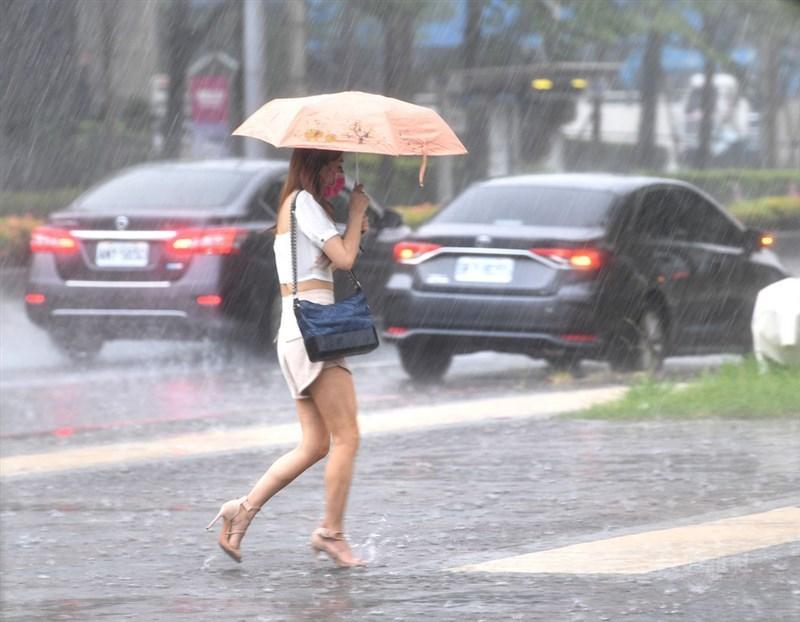 氣象局表示,預估週末2天西南風會增強為西南氣流到達台灣上空,中南部地區易有大雨發生,而南部地區更不排除會有豪雨等級以上的降雨,北部午後也可能有局部大雨發生。台北市29日午後下起大雨,民眾撐傘過馬路。中央社記者王飛華攝 110年7月29日