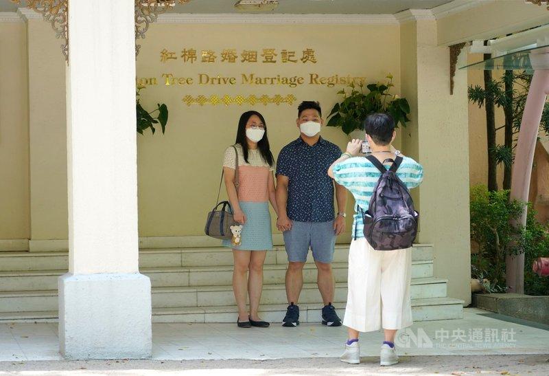 官方統計顯示,2019冠狀病毒疾病(COVID-19)的爆發導致香港2020年的結婚率大幅下降37%。圖為去年農曆七夕,有新人來到香港紅棉路婚姻登記處,並在登記處門口拍照留念。(香港中通社提供)中央社  110年7月30日