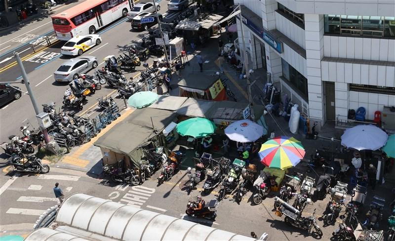 韓國中央防疫對策本部通報,29日新增1710例確診,已連續24天破千例。圖為26日首爾東大門市場外排滿了等候取貨的外送員。(韓聯社)