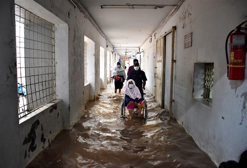 孟加拉官員今天表示,東南部地區洪水與土石流肆虐,已造成數十村莊的超過30萬民眾受困。圖為東南部城市吉大港醫護人員從被洪水侵襲的醫院中救出COVID-19病患。(安納杜魯新聞社)