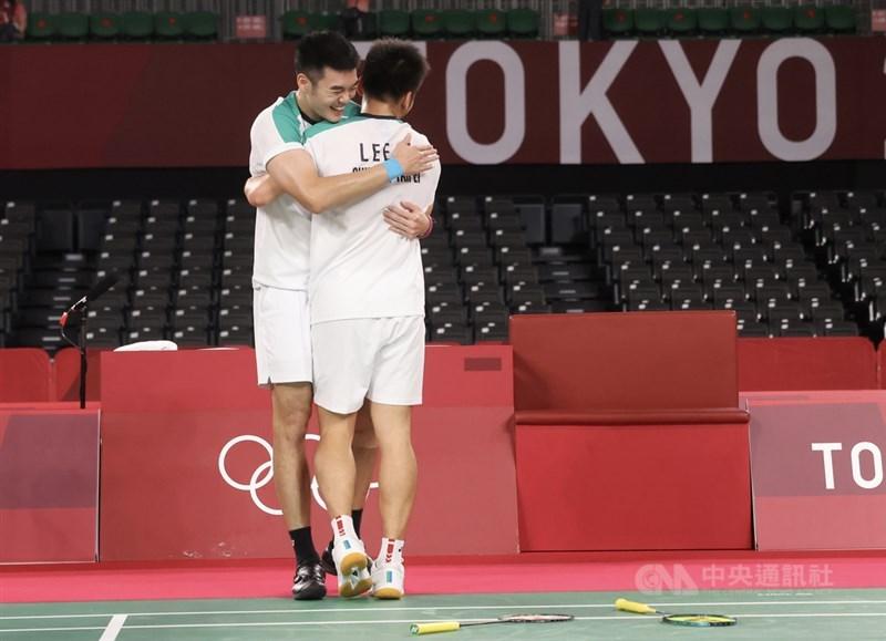 台灣羽球男雙搭檔李洋(背對者)、王齊麟(後)31日晚間出征東京奧運羽球男雙金牌戰,一番激戰成功拍落中國組合,奪下金牌,兩人在確定勝利後開心相擁。中央社記者吳家昇攝 110年7月31日