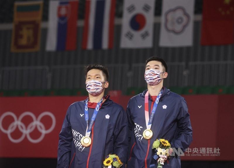 東京奧運羽球男子雙打賽程31日晚間告一段落,台灣「麟洋配」搭檔李洋(左)、王齊麟(右)勇奪台灣奧運羽球史上首面金牌,賽後兩人注視中華隊旗在場中緩緩高升。中央社記者吳家昇攝 110年7月31日